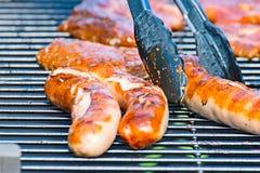 A salsicha do pirralho é servida na grade do carvão vegetal com os tenazes de brasa da grade foto de stock
