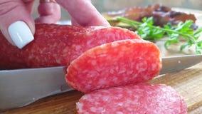 A salsicha do salame cortou com umas guloseimas do movimento lento da faca rústicas vídeos de arquivo