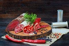 Salsicha e bresaola curado cortado com especiarias e um ramo do explorador de saída de quadriculação fotografia de stock