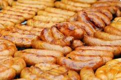 Salsicha fresca e cachorros quentes que grelham fora em uma grade do assado do gás Close up da salsicha na grade imagem de stock royalty free