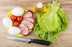 Salsicha fumado, tomates, ovos na placa, óleo vegetal e faca Foto de Stock