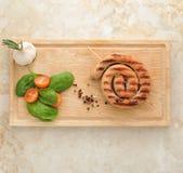 Salsicha grelhada em uma espiral - salsicha de carne de porco em um espeto de madeira, Imagem de Stock