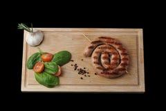 Salsicha grelhada em uma espiral - salsicha de carne de porco em um espeto de madeira, Foto de Stock