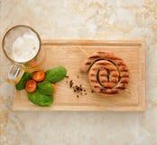 Salsicha grelhada em uma espiral - salsicha de carne de porco em um espeto de madeira, m Fotos de Stock Royalty Free