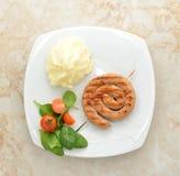 Salsicha grelhada em uma espiral - salsicha de carne de porco em um espeto de madeira, m Fotografia de Stock