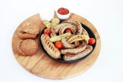 Salsicha grelhada em uma placa de madeira com molho, isolamento Foto de Stock