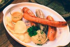 Salsicha grelhada servida com batatas trituradas e molho em um vidro pequeno fotos de stock
