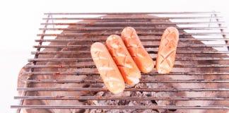 Salsicha grelhada sobre uma grade quente do assado Fotos de Stock Royalty Free