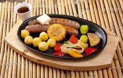 Salsicha que faz roasted com vegetal Imagens de Stock