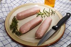 Salsichas britânicas cruas com ervas em uma placa Fotos de Stock