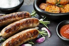 Salsichas com as fritadas dos alecrins e da batata doce Fotografia de Stock