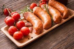 Salsichas com tomates em uma bandeja com especiarias Imagens de Stock Royalty Free