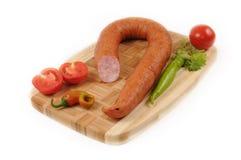 Salsichas com um tomate e uma pimenta na placa de corte imagens de stock