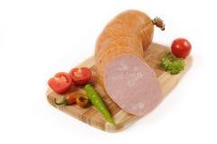 Salsichas com um tomate e uma pimenta na placa de corte foto de stock