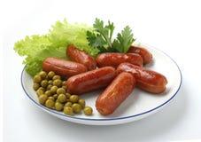 Salsichas cozidas em um prato branco Imagens de Stock