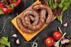 Salsichas cruas frescas na placa de corte Fotografia de Stock