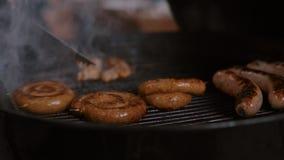 Salsichas da carne da grade do assado no terraço exterior filme