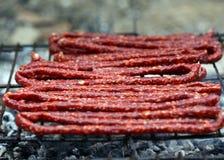 Salsichas da vara em uma grade Fotografia de Stock