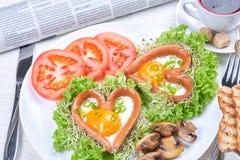 Salsichas dadas forma coração com ovos fritos Foto de Stock Royalty Free