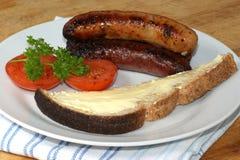 Salsichas de carne de porco, tomate e pão grelhados do brinde Fotografia de Stock Royalty Free