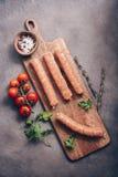Salsichas de carne de porco cruas com tomates de cereja e especiarias em uma placa de corte, fundo r?stico Vista superior, config imagem de stock royalty free
