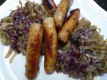 Salsichas de carne de porco grossas e batatas spiralized em uma placa Fotos de Stock Royalty Free