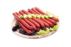 Salsichas deliciosas, decoradas com vegetais Foto de Stock