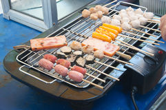 Salsichas do churrasco na grade eletrônica fotografia de stock