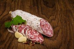 Salsichas do salame em um fundo de madeira Fotografia de Stock