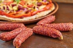 Salsichas do salame isoladas no fim de madeira marrom da tabela acima No fundo borrado cortou a pizza com salame, tomates, piment Fotografia de Stock Royalty Free