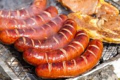 Salsichas e carne de porco grelhadas Imagens de Stock
