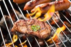 Salsichas e carne do BBQ na grade Fotografia de Stock Royalty Free