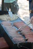 Salsichas e cebolas que cozinham na grade fotos de stock
