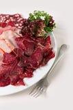 Salsichas e presunto cortados em uma placa Fotos de Stock
