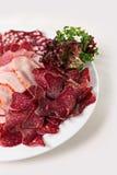 Salsichas e presunto cortados em uma placa Fotografia de Stock Royalty Free