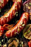 Salsichas e vegetais grelhados com especiarias da adição e as ervas frescas em uma grade Imagens de Stock Royalty Free