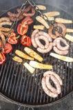 Salsichas e vegetais grelhados em um assado Imagens de Stock Royalty Free