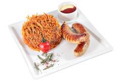 Salsichas fritadas com couve cozido no prato de serviço quadrado, isola Fotografia de Stock Royalty Free