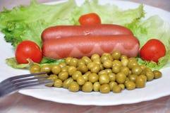 Salsichas fritadas com salada Fotos de Stock
