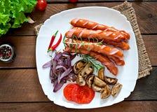 Salsichas fritadas com vegetais Fotografia de Stock