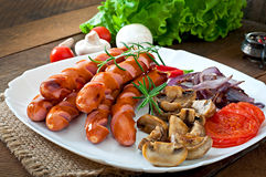 Salsichas fritadas com vegetais Fotografia de Stock Royalty Free