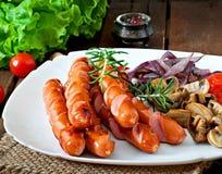 Salsichas fritadas com vegetais Imagem de Stock Royalty Free