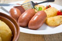 Salsichas fritadas e batatas panadas Fotos de Stock
