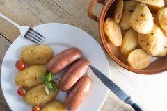 Salsichas fritadas e batatas panadas Fotografia de Stock Royalty Free