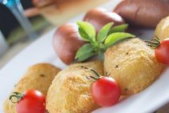 Salsichas fritadas e batatas panadas Imagem de Stock