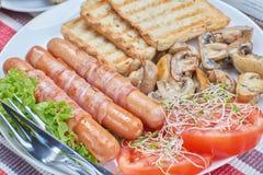 Salsichas fritadas envolvidas no bacon Fotos de Stock