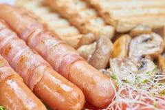 Salsichas fritadas envolvidas no bacon Foto de Stock Royalty Free