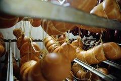 Salsichas fumado Mouthwatering no fundo de uma fábrica da carne fotos de stock royalty free