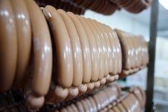 Salsichas fumado Mouthwatering no fundo de uma fábrica da carne imagem de stock royalty free