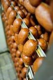 Salsichas fumado Mouthwatering no fundo de uma fábrica da carne fotografia de stock